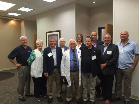 The delegation of visitors from the Western Galilee Cluster, Israel, joined by Sandy Springs City Councilmember Andy Bauman (far left), gathers around Dr. Paul Scheinberg, Emory Saint Joseph's chief medical officer (center), during a Sept. 12 hospital tour. (Photo Grace Huseth)