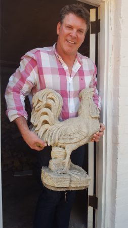 Dr. Robin Fowler holding one of the rooster statues he rescued, and which may have once stood on a lost front gate at the Thornton House. (Photo John Ruch)