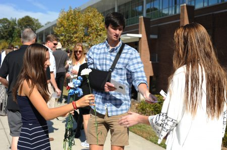 Dunwoody High School seniors Patrick Clinch and Ally Womble pass out programs and flowers at the school's Tree Dedication Ceremony held Oct. 30 in memory of former Dunwoody High students. (Photo Phil Mosier)