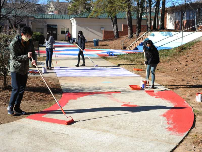 Elijah Nicpon, left, and Esha Bhat join volunteers painting a mural design on a courtyard path at the Spruill Center for the Arts.
