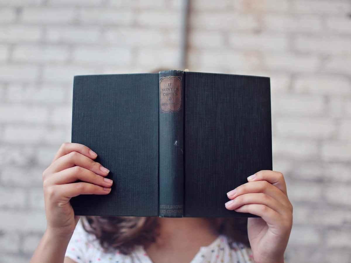 selective focus photography of woman holding book