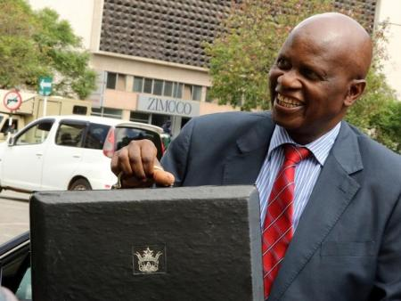 Minister of Finance Patrick Chinamasa carries the briefcase containing the 2017 National Budget at the Parliament in Harare, Zimbabwe December 8, 2016. REUTERS/Philimon Bulawayo