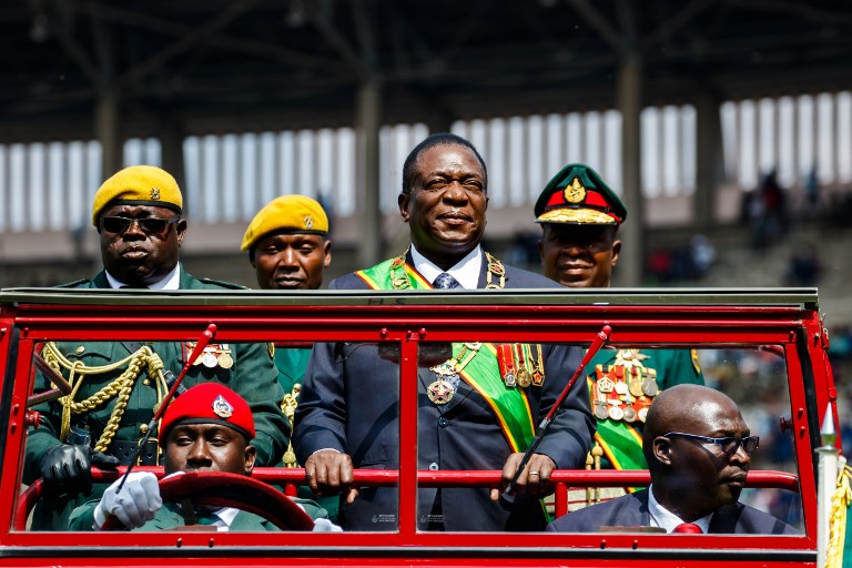 Report Focus News : Zimbabwe's President Emmerson Mnangagwa (C) inspects the guard of honour from a car during the Defence Forces Day celebrations held at the National Sports Stadium in Harare on August 14, 2018. / AFP PHOTO / Jekesai NJIKIZANA