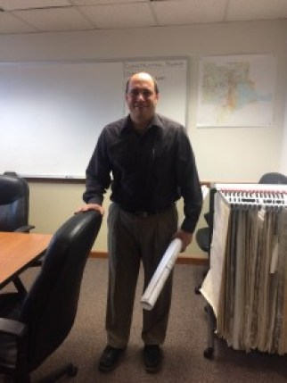 City engineer Jim Bowling stands in his office with document in hand. Photo by Elizabeth Randolph.