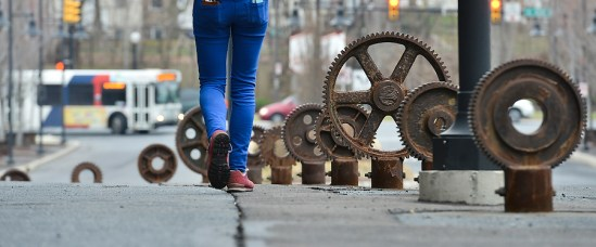 Former machine parts from the steel mill have been set into the sidewalks at various spots.