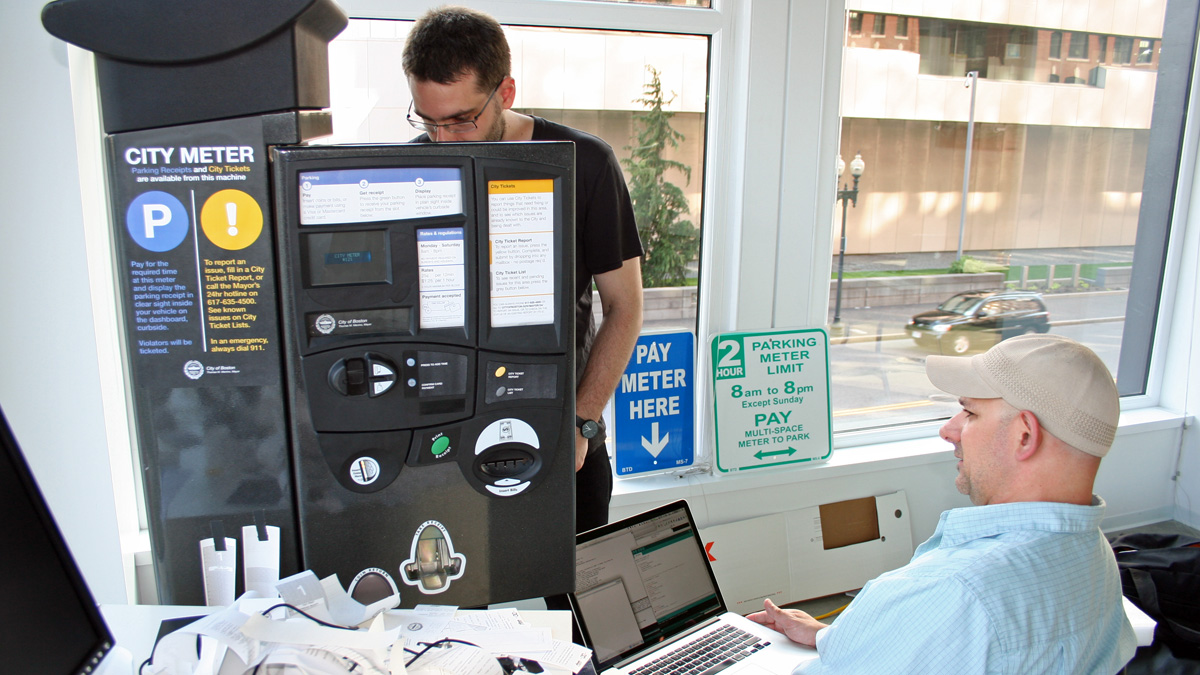 Mayo Nissen (left) and Brian Del Vecchio (right) at work reprogramming a Multispace Parking Pay Unit