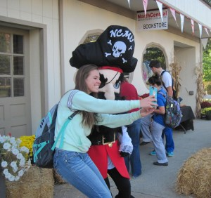"The North Central Missouri College Bookstore participated in National Student Day last week, supporting children's literacy with a variety of activities. Students, including Jessica Farmer of Polo, pictured above with Patch the Pirate, snapped ""selfies"" at the college bookstore and posted to a social media site with #giveme5nsd in order to be entered to win a $500 store gift card. For every entry accepted, ""Reading is Fundamental"" received $1 (up to $5,000). The contest continues through this Thursday. Other student prizes included water bottles given at the Ketcham Community Center and a $50 gift certificate provided by the NCMC Bookstore. Various prizes and food were provided by departments on campus, including the development office, the Alexander Student Center, Student Support Services, the Academic Resource Center and the NCMC Library. Several local businesses donated to NSD as well and $1,400 in prizes were awarded to 100 students on campus. Activities during NSD included a Tenzi dice game, a scavenger hunt and a team building obstacle course for groups to work together to achieve the goal-a popular activity provided by the Missouri National Guard. Patch the Pirate, NCMC mascot, also celebrated NSD by posing with students in their selfies, dancing, and participating in activities. The men's basketball team sold grilled hot dogs and water to students, staff and community members. People could pull up and order lunch from the curb and some were very inspiring with their generosity. The Baptist Student Union also greeted students and provided free lunch to NCMC students."