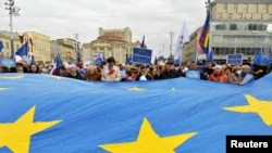 People hold a large EU flag during a rally in support of Poland's membership in the European Union in Katowice, Poland, Oct. 10, 2021.