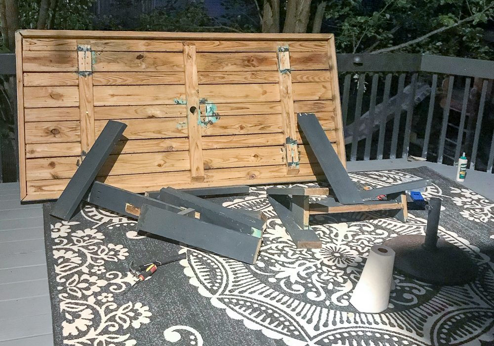 farmhouse table with legs broken off laying on its side on a deck with a black rug