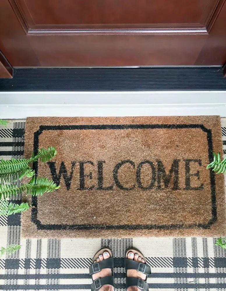 welcome mat layered with buffalo check rug