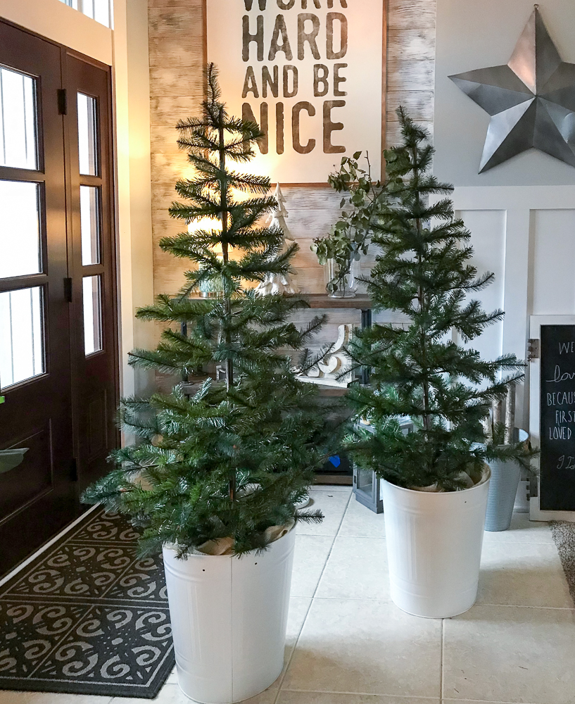 two christmas trees in white buckets in foyer