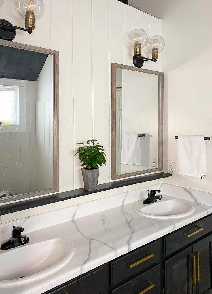 Master bathroom with 2 mirrors a shelf and plant after makeover projects