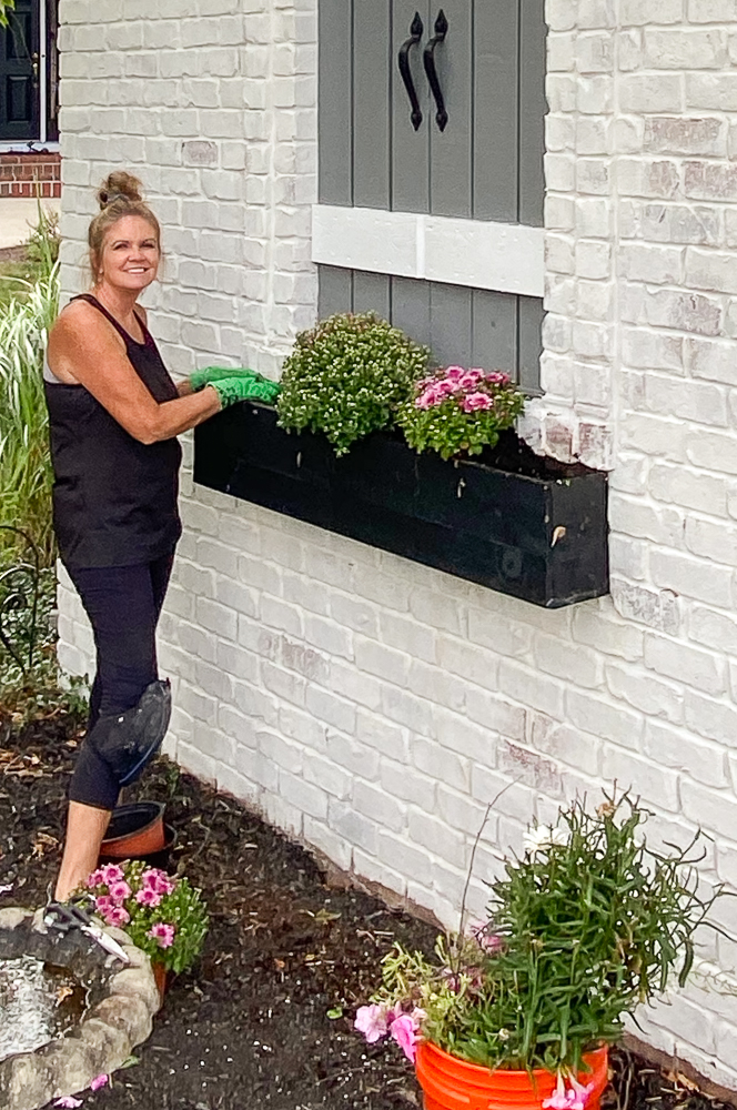 Girl standing next to flower box planting Fall flowers