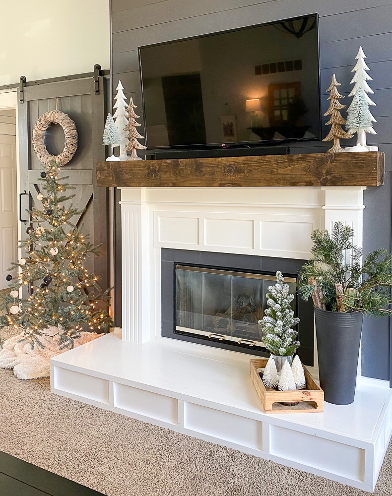 fireplace with Christmas decor and a sliding barn door next to it
