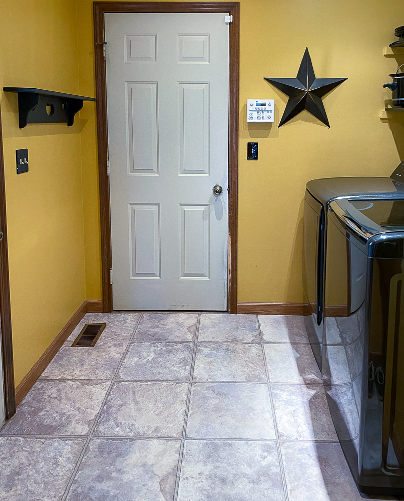 Dated laundry room painted yellow with a large metal star and a shelf