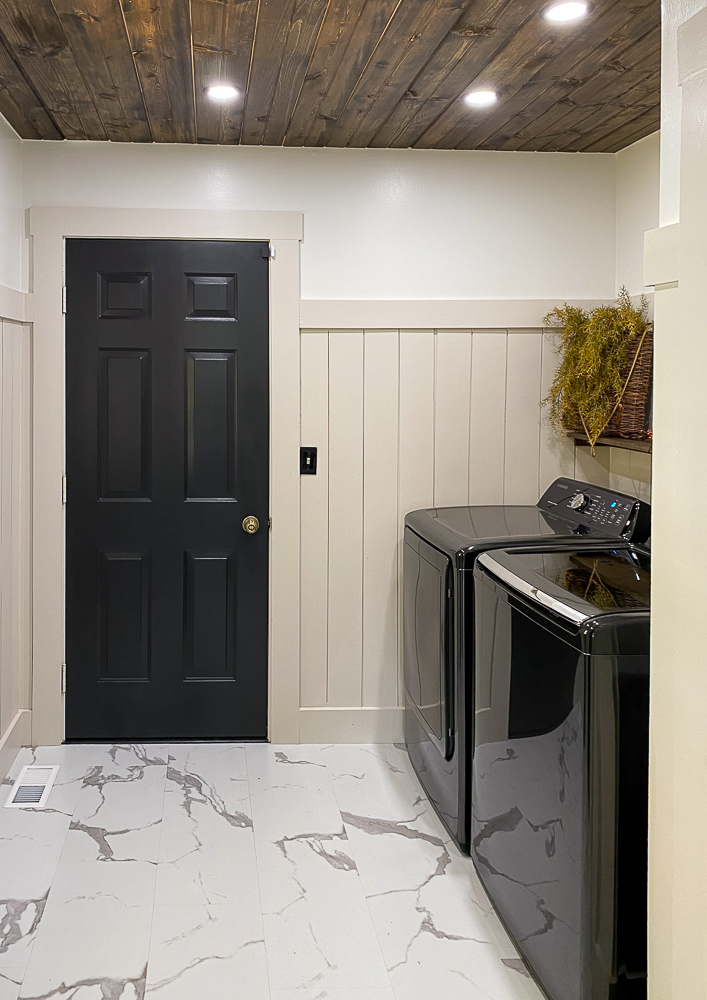 Laundry room with black washer and dryer with a shelf above it and decor