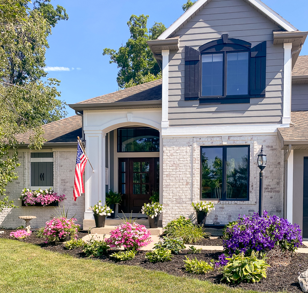 Front of house decked out for fall with mums and pumpkins