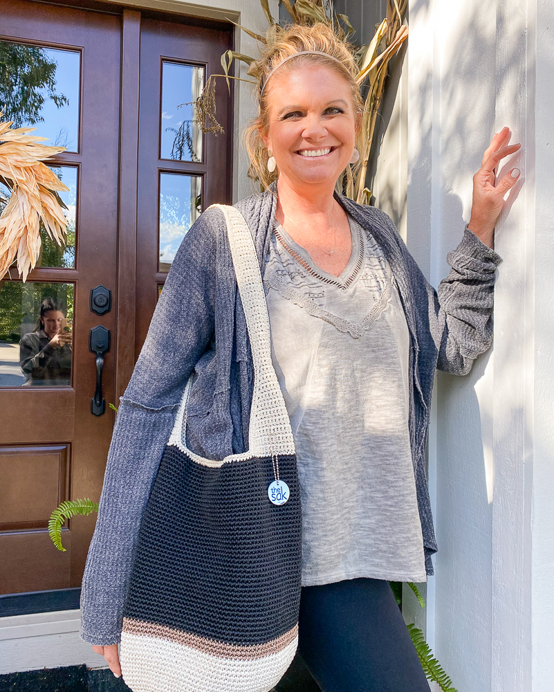 A lady standing on a front porch with a handbag