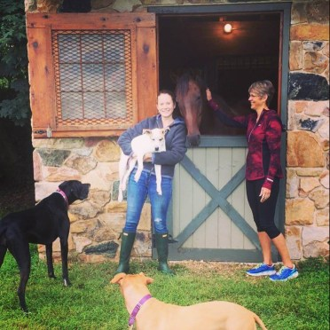 happy Lauryn standing out front of stables with her adorable dogs and horse