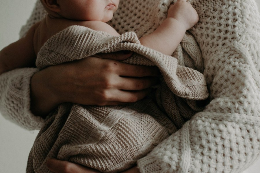 The American Academy of Pediatrics (AAP) recommends keeping soft objects and loose bedding out of the sleeping area for at least the first 12 months. This recommendation is based on data around infant sleep deaths and guidelines for reducing the risk of SIDS.
