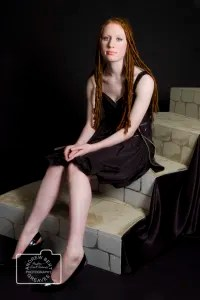 Portrait of a young woman with red hair sat on steps in a studio
