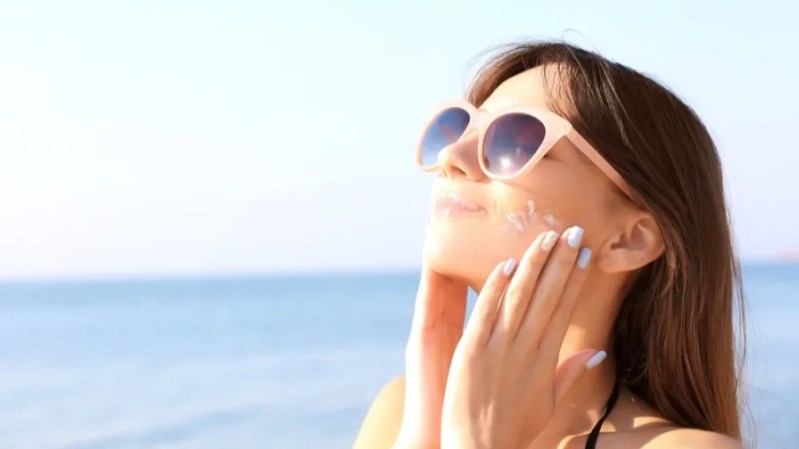 Woman in sunglasses putting on sunscreen by the sea.