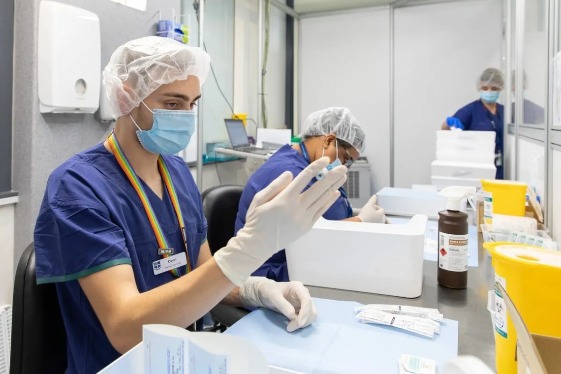 Two pharmacy students preparing vaccine vials at Royal Melbourne Hospital's COVID vaccination hub