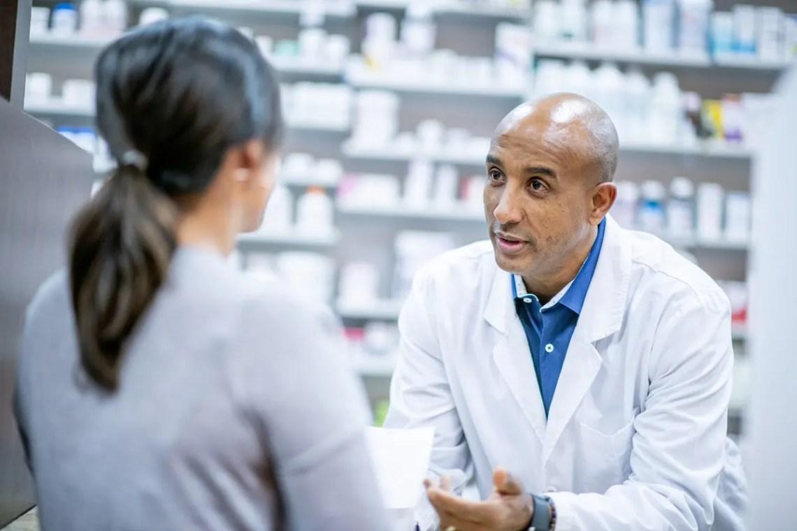 A male pharmacist talking to a female customer