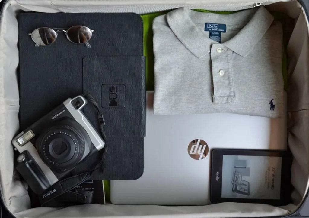 un paio di occhiali da sole dalle lenti arrotondate, una fotocamera istantanea (Polaroid 360) una camicia, un pc hp, un ebook reader