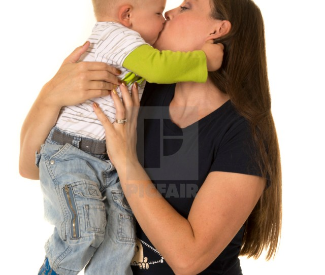 Pregnant Mom With Boy Standing On Lap Kiss Stock Image