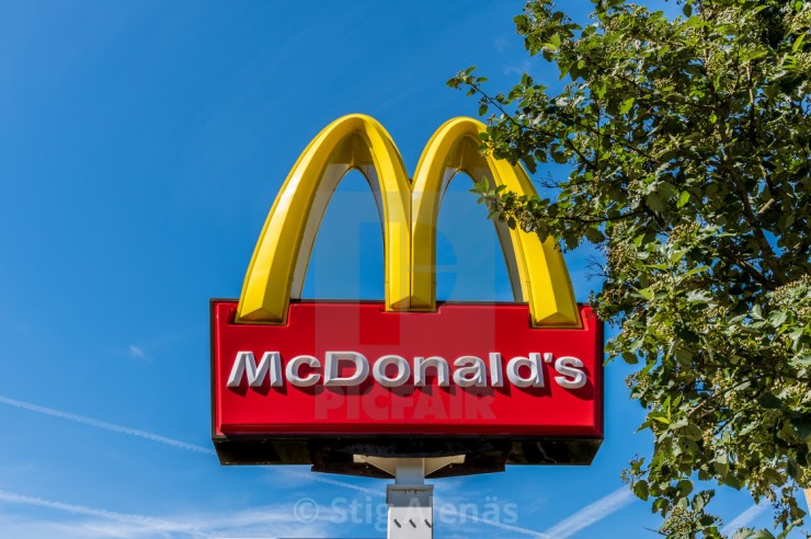 two golden bows, sign of MacDonald´s restaurant beside a green ...