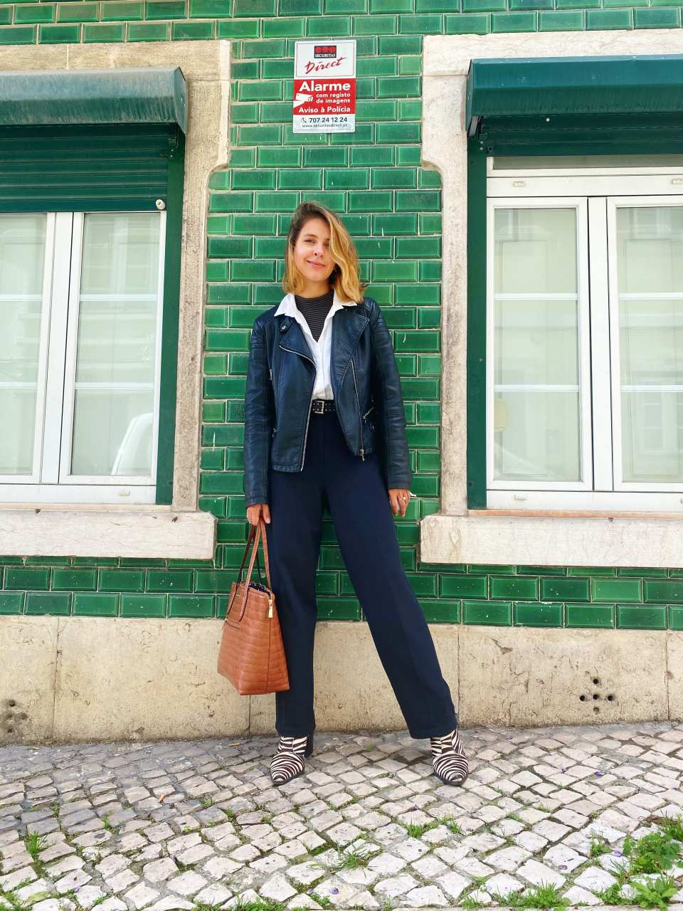 Marcie está posando em frente a um prédio com tijolos verde esmeralda e janelas brancas. O look é composto por turtle neck listrada usada por baixo de uma camisa branca com gola pra fora, jaqueta de couro preta biker, calça de alfaiataria preta, bolsa de croco caramelo e bota peluda de zebra.
