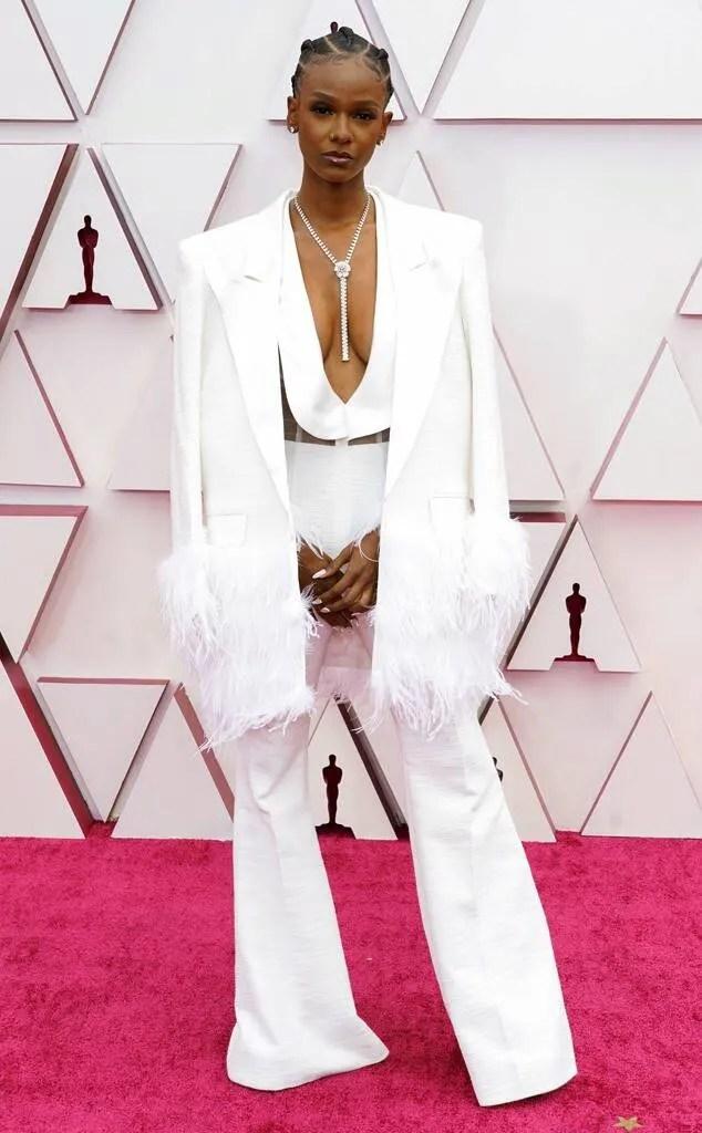 Foto com Tiara Thomas no red carpet do Oscar 2021. O look é composto por macacão branco decotado até o umbigo com lapelas largas e calça de alfaiataria, colar gravata prateado e blazer branco nos ombros, com mangas e barra com plumas. Os cabelos estão trançados para trás.