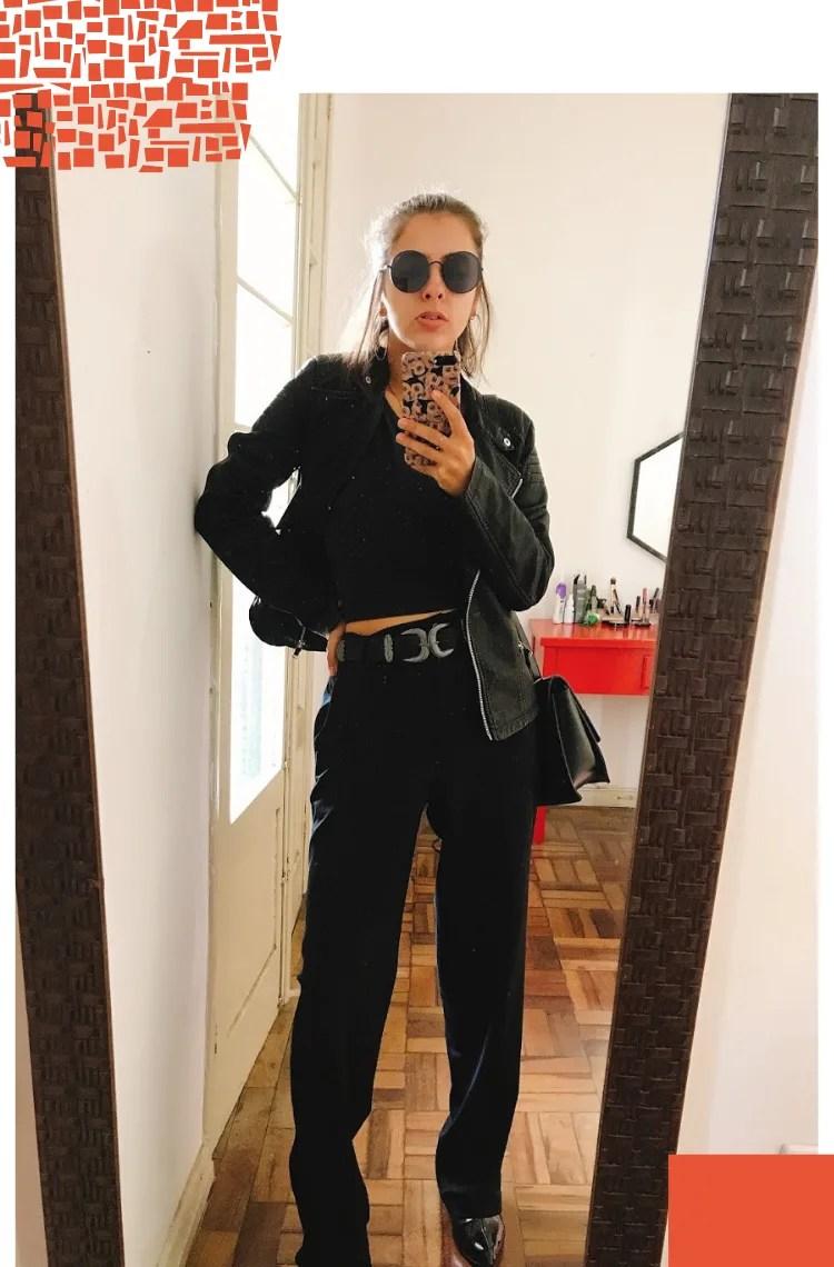Foto vertical com moldura branca. Na foto, Marcie se fotografa em frente a um espelho com moldura marrom. O look é composto por óculos escuros pretos, cropped preto, jaqueta biker de couro preta, calça de alfaiataria preta e cinto western.