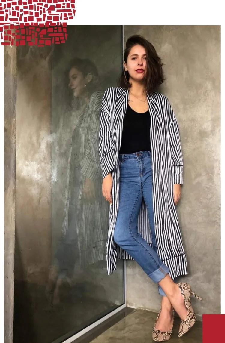Foto vertical com moldura branca. Na foto, Marcie posa de pé com uma perna cruzada em frente a uma parede cinza. O look é composto por camiseta preta, quimono listrado preto e branco, jeans com barra dobrada e scarpin com estampa de cobra.