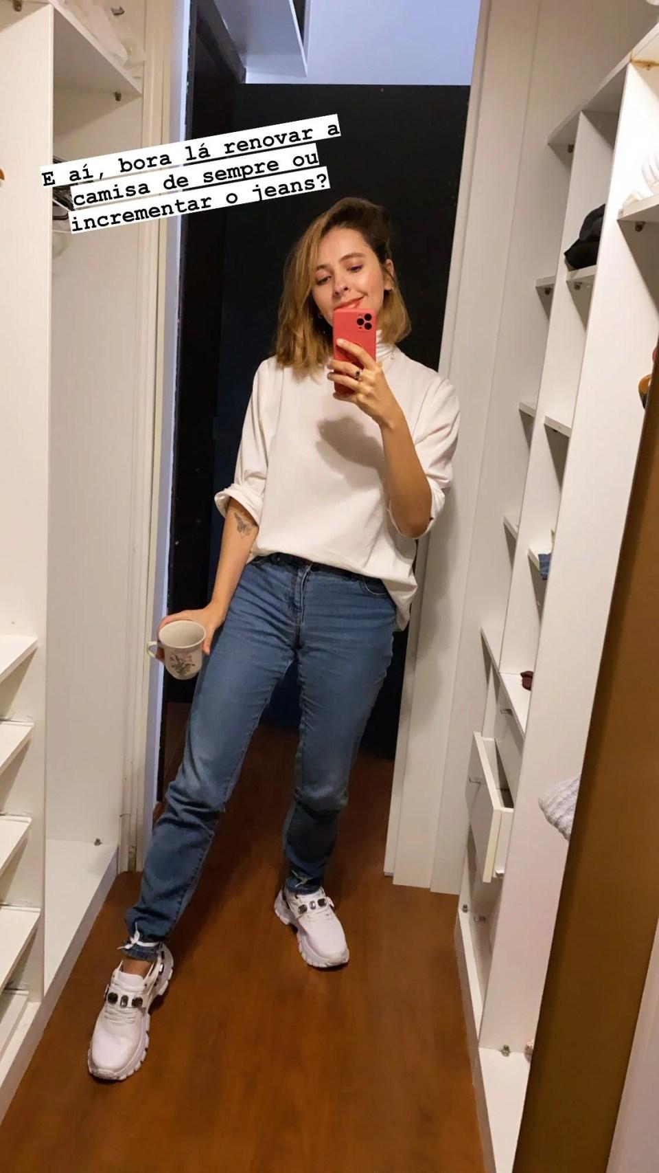 Marcie se fotografa em um espelho com o celular na mão. O look é composto por camisa branca virada, com a parte de trás usada para a frente, como se fosse uma turtle neck, calça jeans e tênis chunky branco com os cadarços amarrados na barra da calça.