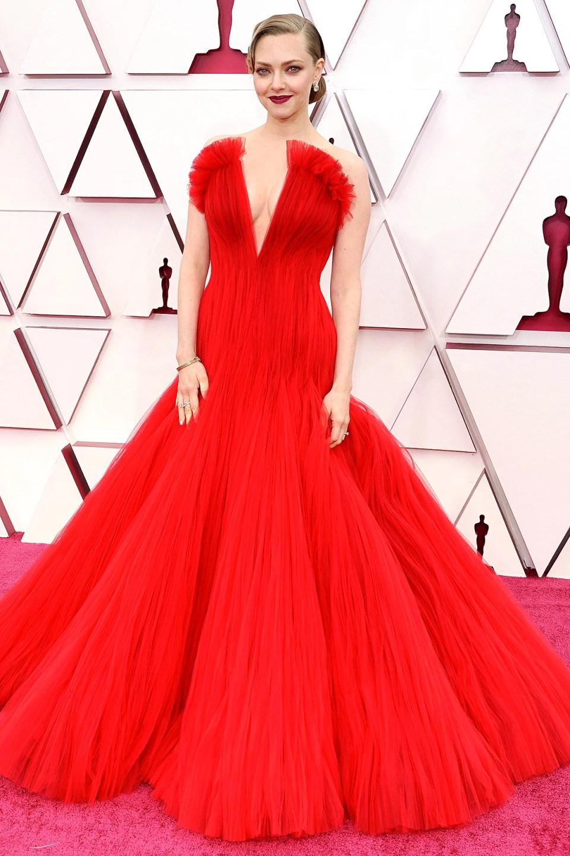 Foto mostrando o look de Amanda Seyfried no Oscar 2021. Ela usa um vestido vermelho sem alças de tule inteiramente plissado com um corte sereia com muito volume na barra. Um coque baixo e make em tons de vermelho e bordô finaliza o visual.