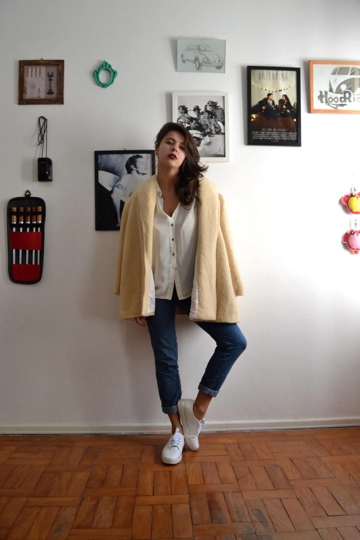 Marcie posa em frente a uma parede branca com vários quadros pendurados. O look é composto por camisa branca, calça jeans, casaco amarelo de lã nos ombros e tênis branco.