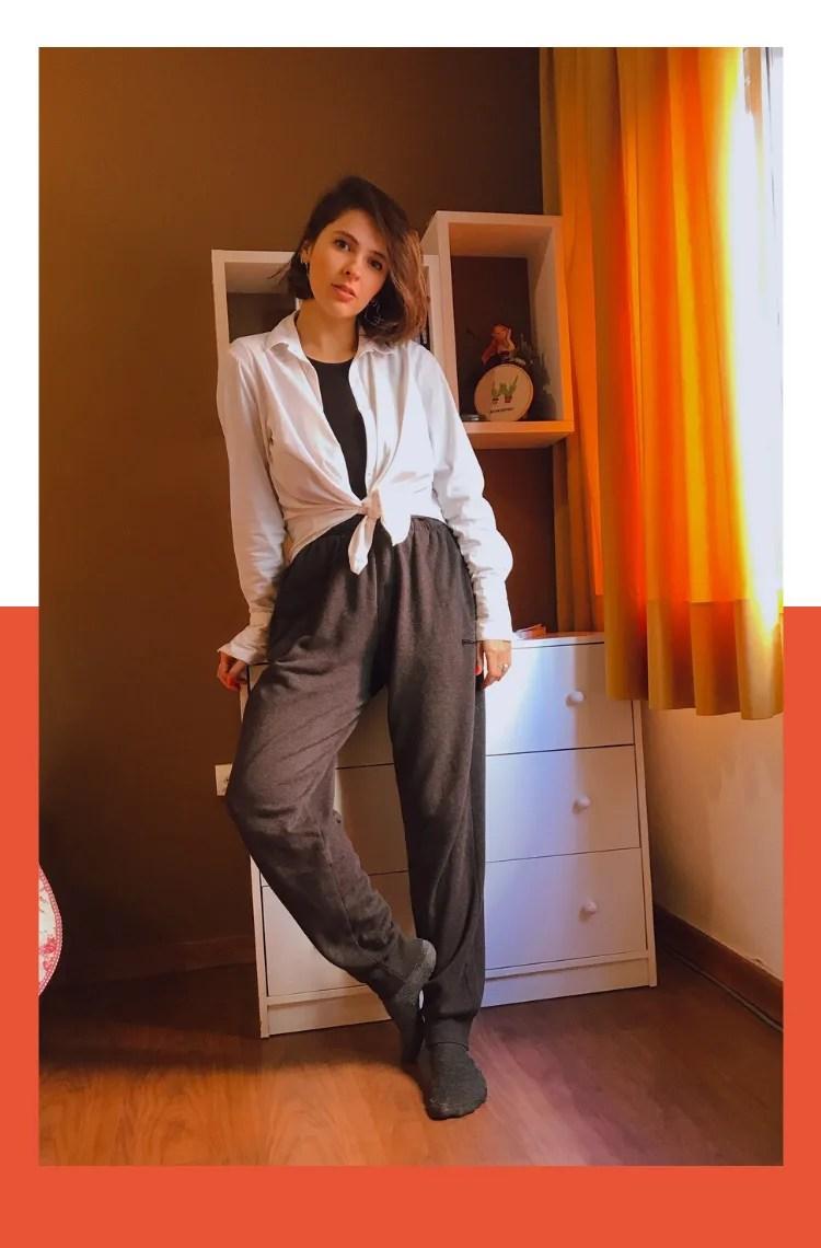 Foto vertical com moldura branca de cima até a metade e laranja da metade para baixo. Na foto, Marcie está escorada em uma cômoda branca com três gavetas, em frente a uma parede marrom. No seu lado direito, uma cortina laranja e iluminação da janela entra. O look é composto por calça de moletom cinza, meia cinza, camiseta de mangas longas preta e camisa branca usada aberta apenas amarrada na cintura.