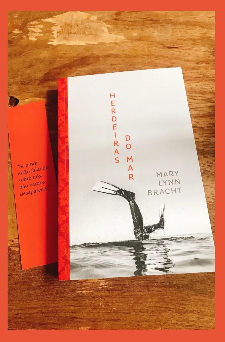 Foto vertical com fundo laranja. Na foto, está uma mesa de madeira, com o livro herdeiras do mar em cima da mesa.