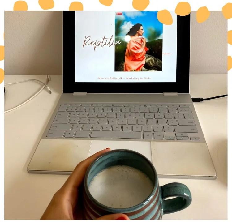 Foto com moldura branca e poá oversized amarelo. Na foto está um notebook com um ppt e o texto Reptilia, e uma caneca de cerâmica listrada com café e espuma de leite.