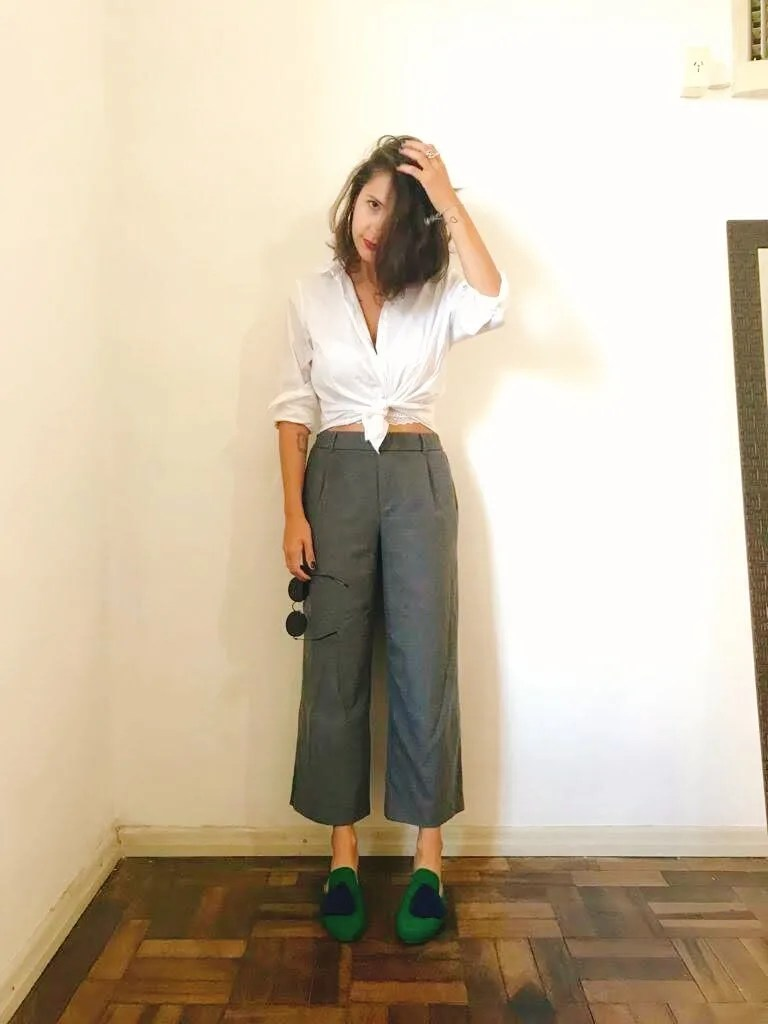 Marcie posa em frente a uma parede branca olhando para a câmera, com a mão no cabelo. O look é composto por camisa branca amarrada na cintura, com sutiã branco na barra, calça de alfaiataria pantacourt cinza de lã e mule verde com pompom azul.