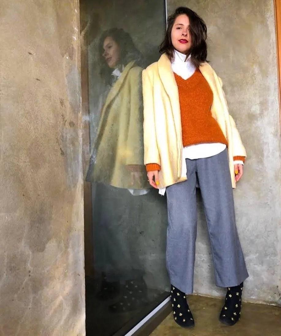 Marcie posa em frente a uma parede cinza com vidro. O look é composto por camisa branca usada por baixo de um blusão mostarda com gola v, casaco amarelo de lã, pantacourt cinza de lã e bota preta com bordado dourado.