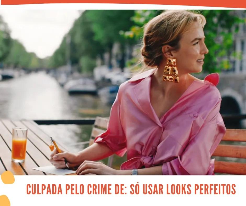 """Montagem com fundo branco, uma foto central. No topo inferior, uma listra laranja decora a imagem. Na foto, Villanelle está sentada em frente a um canal, escrevendo em uma mesa de madeira. Embaixo da foto, as palavras """"CULPADA PELO CRIME DE: SÓ USAR LOOKS PERFEITOS""""."""