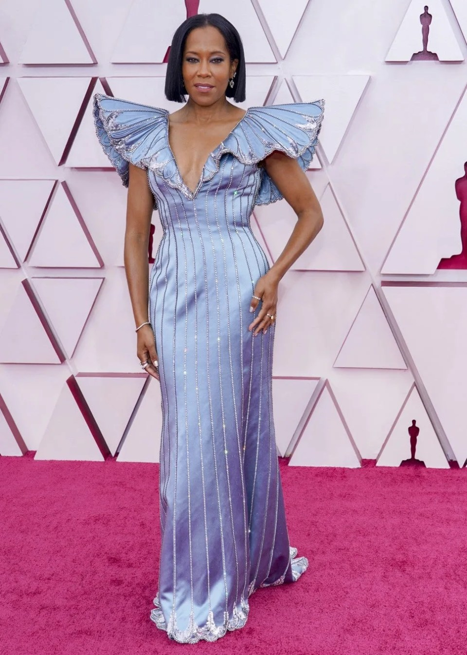 Foto do look de Regina King no red carpet do Oscar 2021. Ela veste um vestido azul claro acetinado longo com decote v profundo e mangas amplas altas, que parecem asas de borboletas. O vestido tem linhas verticais feitas com cristaias e lantejoulas. O cabelo está liso na altura dos ombros, com brincos discretos de cristais.