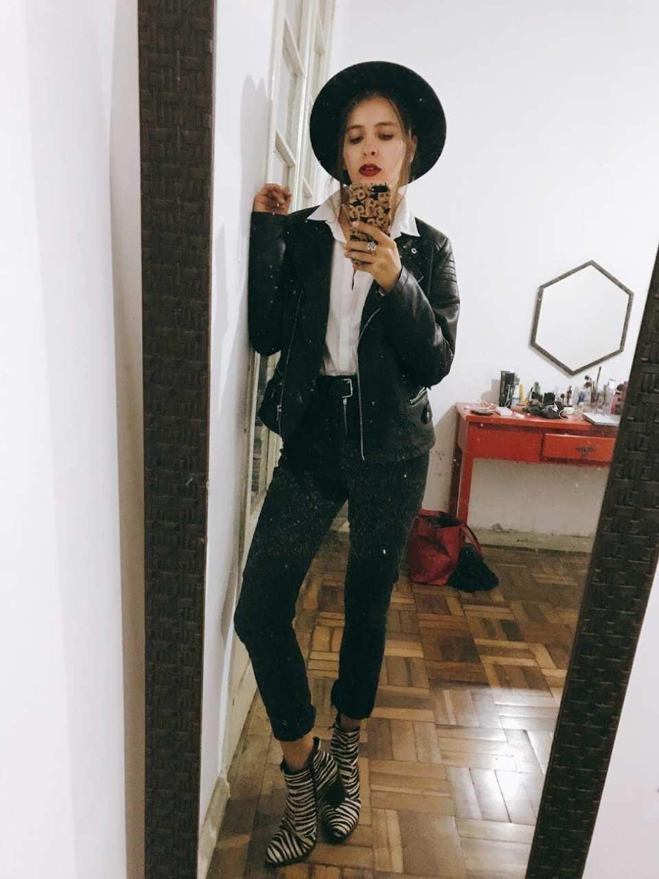 Marcie posa em frente a um espelho com celular na mão. O look é composto por chapéu preto com cabelo preto, camisa branca, jaqueta de couro, calça skinny preta com cinto preto e bota de zebra com pelinhos.