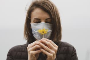 mujer de frente con cubrebocas y flor en sus manos por coronavirus