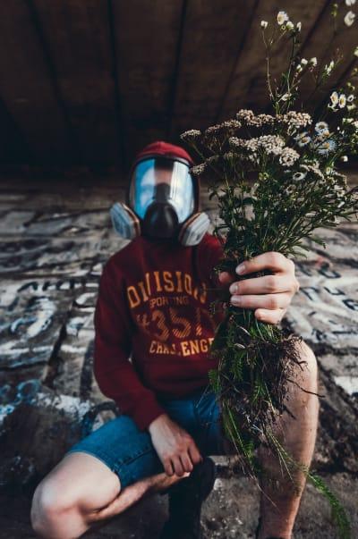 Hombre en cuclillas con una máscara antigases sosteniendo un ramo de flores.