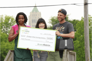 Su Lok, Director, Corporate and Community Partnerships presents a $40,000 grant from ScottsMiracle-Gro to Michigan Urban Farming Initiative Co-Founder and President, Tyson Gersh and Farm Manager, Pinky Jones during the GRO1000 event.