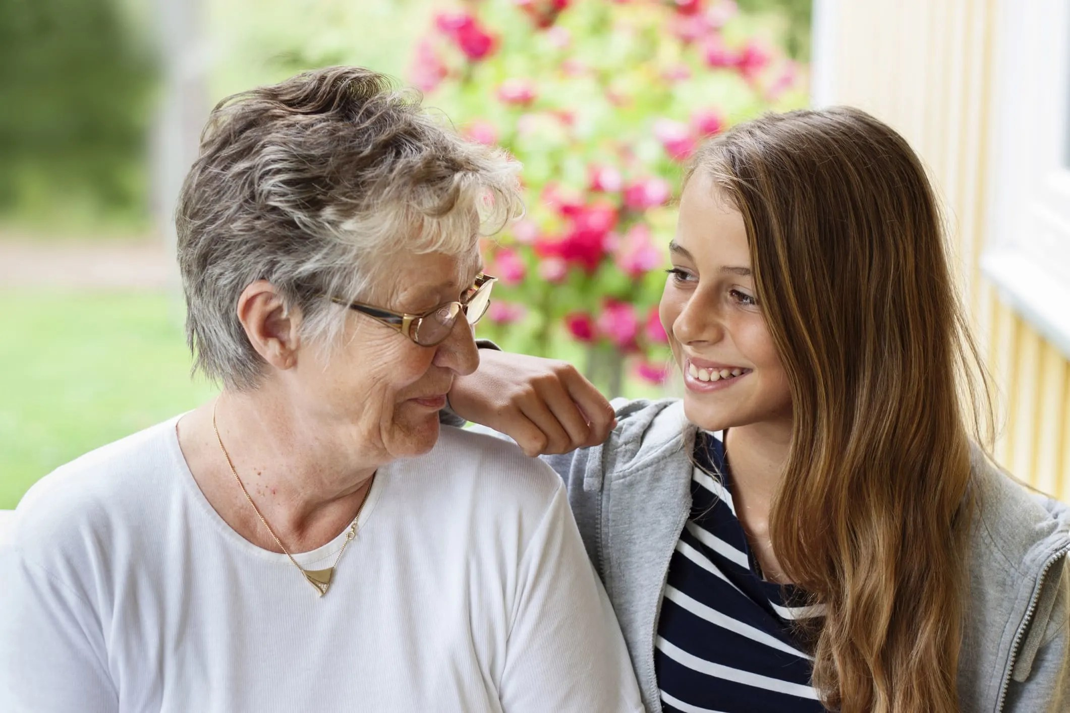 Older woman with teenage girl, smiling at each other